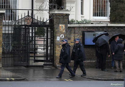 Police officers walk past the Russian embassy in London, Britain, March 12, 2018.