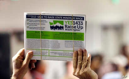 FILE - A supporter holds up a petition for Initiative 1433, a ballot measure to raise Washington state's minimum wage and allow all workers in the state to earn paid sick leave, March 22, 2016, in Everett, Wash.