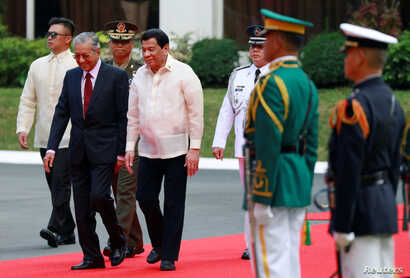 Philippine President Rodrigo Duterte and Malaysian Prime Minister Mahathir Bin Mohamad walk together during the welcoming ceremony for the Malaysian leader at the Malacanang presidential palace in Manila, Philippines, March 7, 2019.