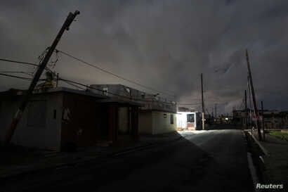 A house is lit with the help of a generator, on a street in the dark after Hurricane Maria damaged the electrical grid in September 2017, in Naguabo, Puerto Rico, Jan. 25, 2018.
