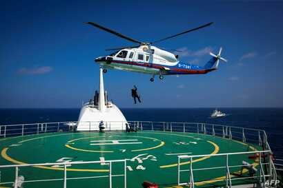 FILE - Helicopter rescue crew members practice rescue techniques during an emergency drill held by Sansha city's maritime search and rescue center in the South China Sea near Sansha, in south China's Hainan province, July 14, 2016.