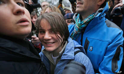 Freed feminist punk group Pussy Riot member Yekaterina Samutsevich, center, smiles as she speaks outside a court in Moscow, Wednesday Oct. 10, 2012.