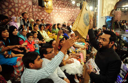 FILE - Pakistani television show host Aamir Liaquat Hussain, right, distributes gifts to the audience during an Islamic quiz show in Karachi, July 31, 2013.