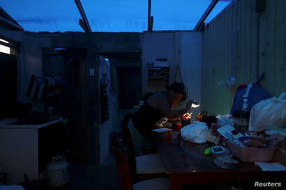 A woman uses a flashlight while trying to connect a transformer to a car battery, after Hurricane Maria hit the island in September 2017, in Maunabo, Puerto Rico, Jan. 27, 2018.