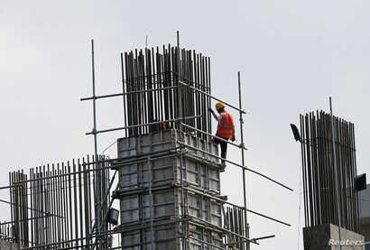 A laborer works at a construction site of an apartment complex in Colombo March 8, 2016. Sri Lankan Prime Minister Ranil Wickremesinghe, saying his country must break out of a debt trap, on Tuesday announced a rise in value added tax (VAT) and said t...