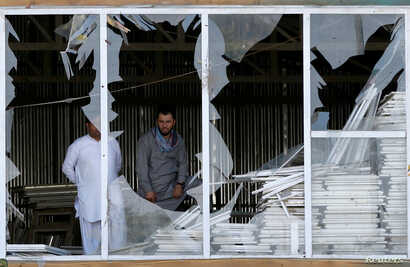 Afghan men look outside a broken window at the site of a suicide attack in Kabul, Afghanistan, Sept. 9, 2018.