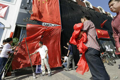 Workers at a Japanese restaurant cover up the shop front with Chinese national flags and red clothes ahead of major protests expected on Tuesday in Beijing, China, September 17, 2012.