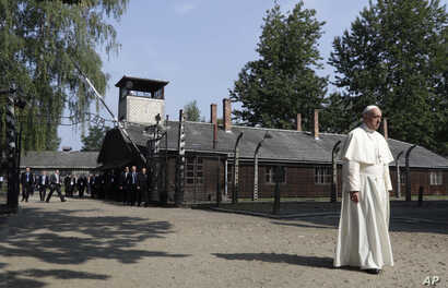 Pope Francis walks through the gate of the former Nazi German death camp of Auschwitz in Oswiecim, Poland, Friday, July 29, 2016.