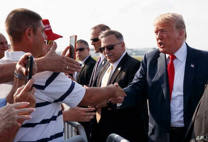 President Donald Trump greets supporters as he arrives on Air Force One at John Glenn Columbus International Airport in Columbus, Ohio, Aug. 4, 2018, en route to a rally at Olentangy Orange High School in Lewis Center, Ohio.