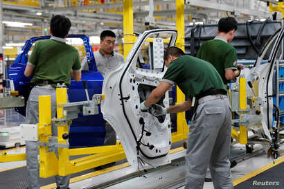 FILE - Employees work at the production line inside the Chery Jaguar Land Rover plant phase 2 after the phase 2 opening ceremony in Changshu, Jiangsu province, China, June 27, 2018.