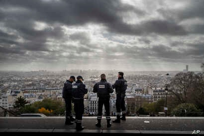 Paris is seen as French police officers stand on guard near the church of Sacre Coeur, on top of the Montmartre hill, in Paris, Nov. 18, 2015.