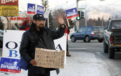 An unnamed homeless person waives soliciting money amongst political campaign sign wavers in Anchorage, Alaska in 2008.  Nearly 45 percent of homeless in that state are Alaska Native, some, like this man, U.S. military veterans.