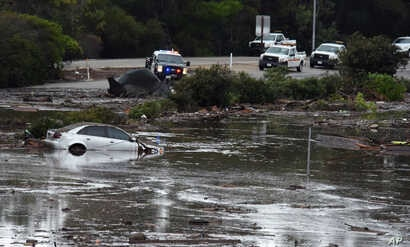 This photo provided by the Santa Barbara County Fire Department shows the U.S. Highway 101 at the Olive Mill Road overpass flooded with runoff water from Montecito Creek in Montecito, Calif., Jan. 9, 2018.