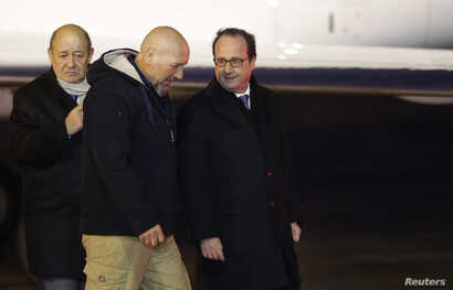 FILE - Former hostage Serge Lazarevic (C) talks with then-French president Francois Hollande (R) and then-defense minister Jean-Yves Le Drian at his arrival at a military airport near Paris, France, Dec 10, 2014. Lazarevic had been kidnapped by al-Qa...