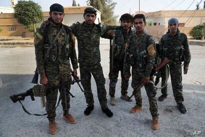 FILE - In this July 22, 2017, photo, Arab and Kurdish fighters with the U.S.-backed Syrian Democratic Forces (SDF), pose for a picture as they prepare to move to the front line to battle against the Islamic State militants, in Raqqa, northeast Syria