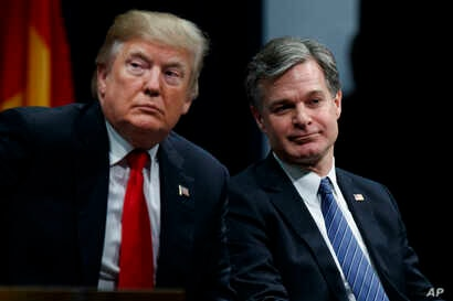 FILE - President Donald Trump sits with FBI Director Christopher Wray during the FBI National Academy graduation ceremony in Quantico, Va.