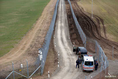A Hungarian police and soldiers patrol the Hungary-Serbia border, which was recently fortified by a second fence, near the village of Gara, Hungary, March 2, 2017.