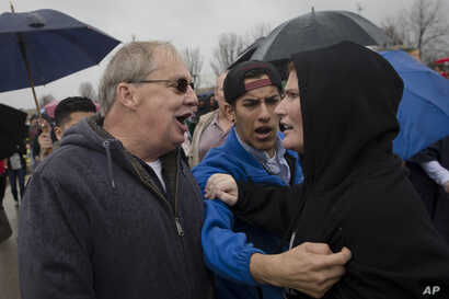 FILE - A Donald Trump supporter, left, and a protester argue before the candidate's arrival in West Chester, Ohio, March 13, 2016. Democratic and Republican views of the opposing political party have sunk to such lows that many say their rivals make ...