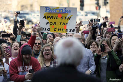 Supporters of U.S. Democratic presidential candidate Bernie Sanders cheer as he speaks to the overflow crowd at a town hall event in Appleton, Wisconsin, March 29, 2016.