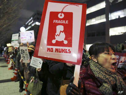 Protesters hold placards during an anti-nuclear rally near the Prime Minister's office in Tokyo, March 11, 2016.