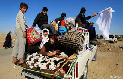 Iraqis fleeing the conflict in Kokjali are seen on the road east of Mosul, Iraq Nov. 3, 2016.