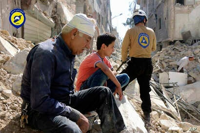 In this picture provided by the Syrian Civil Defense group known as the White Helmets, residents sit amongst rubble in rebel-held eastern Aleppo, Syria, Oct. 11, 2016.