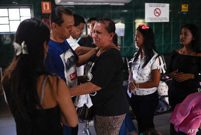 People bid farewell to relatives before boarding a bus at a station in Caracas, Venezuela, Jan. 3, 2019.