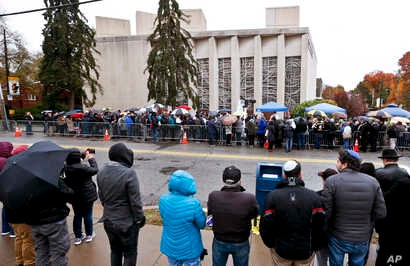 "People line both sides of the street as they gather outside the Tree of Life synagogue for a service on Nov. 3, 2018, in Pittsburgh. About 100 people gathered in a cold drizzle for what was called a ""healing service"" outside the synagogue that was th..."
