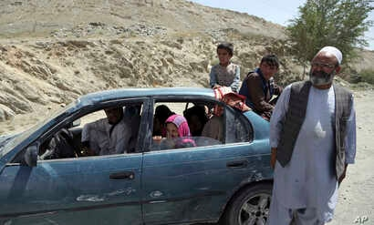 An Afghan family, who have escaped from the volatile Ghazni province, stop at a checkpoint in Maidan Shar, west of Kabul, Aug. 13, 2018.