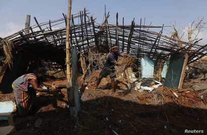 FILE - A fisherman and his wife clear the debris from their damaged house after Cyclone Phailin hit Gopalpur village in Ganjam district in the eastern Indian state of Odisha, Oct. 14, 2013.