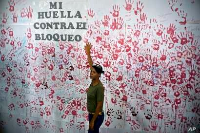 A woman poses in front of hand prints on a wall during an event against U.S. trade embargo against Cuba in Havana,   Oct. 31, 2018. The United Nations will vote Nov. 1 on a resolution regarding the ongoing U.S. trade embargo against Cuba.