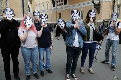 FILE - People wear face masks depicting the Big Brother character from George Orwell's novel 1984, as they attend a protest rally in support of greater Internet freedom, in St.Petersburg, Russia, July 16, 2017.
