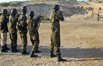 FILE - Somali government forces at a police center in Mogadishua's Hamar Jajab district prepare to shoot a former soldier who was found guilty of intentionally shooting and killing another soldier, June 4, 2011.