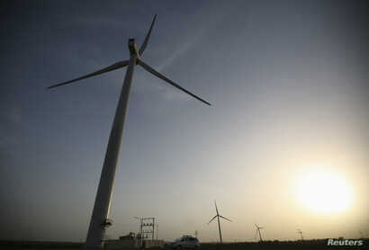 FILE - Power-generating windmill turbines are pictured during the inauguration ceremony of the 25-megawatt ReNew Power wind farm at Kalasar village in the western Indian state of Gujarat, May 6, 2012.