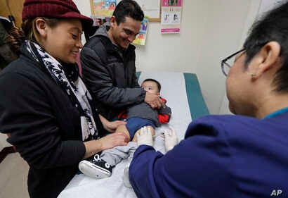 Matilde Gonzalez, left, and Cesar Calles, hold their son, Cesar Julian Calles, 10-months old, as Ana Martinez, a medical assistant at the Sea Mar Community Health Center, gives him a flu shot, Jan. 11, 2018 in Seattle.