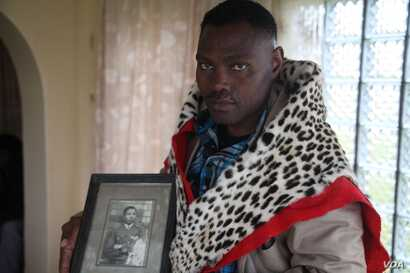 """Chief Zanomthetho Mtirara poses with his leopard skin and a young picture of his adoptive """"grandfather"""" Nelson Mandela, who was taken in by the Thembu royal family at the age of 9 when his father died. A leopard skin like this one will be draped over..."""