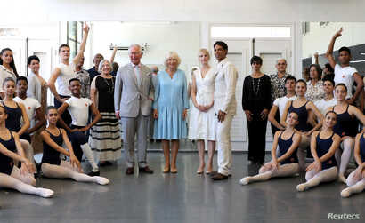 Britain's Prince Charles and Camilla, Duchess of Cornwall together with Carlos Acosta, founder and director of Acosta Danza pose with staff and ballet dancers during a visit to the Acosta Dance Company in Havana, March 25, 2019.