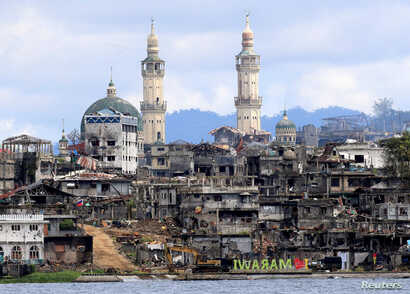 "FILE - A sign that reads ""I love Marawi"" is seen in front of damaged houses, buildings and a mosque inside a war-torn Marawi city, southern Philippines, Oct. 26, 2017."