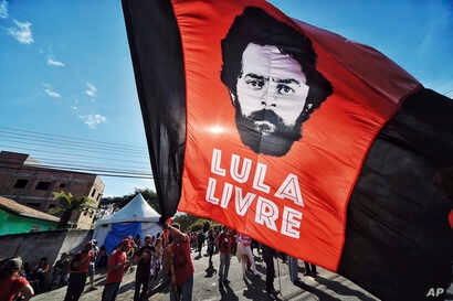 """FILE - A supporter of former Brazilian President Luiz Inacio Lula da Silva waves a banner decorated with an image depicting da Silva and message that reads in Portuguese: """"Free Lula,"""" in front of the Federal Police Department where he is serving jail..."""