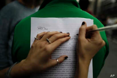 A woman fills out a form to renounce her religious affiliation in Buenos Aires, Argentina, Aug. 18, 2018. People renounced their religion nationwide after a bill to legalize elective abortions in the first 14 months of pregnancy was rejected by senat...