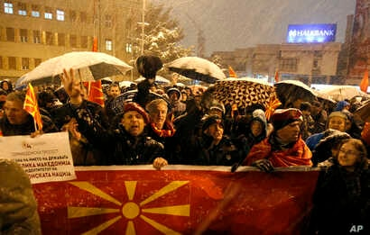 People carry banners and wave flags during a protest against the change of the country's constitutional name, in front of the Parliament building in Skopje, Macedonia, Feb. 27, 2018.