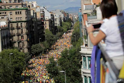 A woman takes photos from a balcony during march to celebrate Catalan National Day in Barcelona, Spain, Sept. 11, 2017.