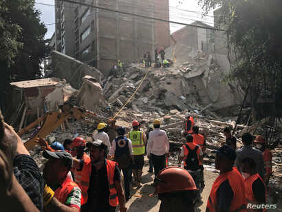 People clear rubble after an earthquake hit Mexico City, Mexico, Sept 19, 2017.