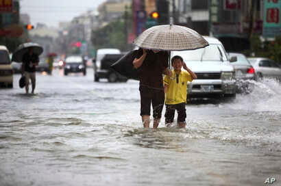 FILE - Local residents walk through floodwaters from passing Tropical Storm.