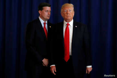 FILE - White House Staff Secretary Rob Porter (L) reminds U.S. President Donald Trump he had a bill to sign after he departed quickly following remarks at his golf estate in Bedminster, New Jersey U.S., Aug.12, 2017.