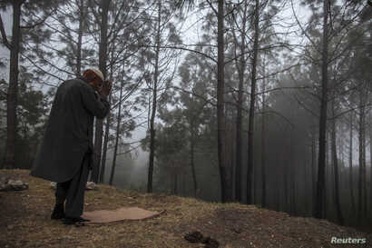A man prays in the mist on Margalla Hills in Islamabad Nov. 6, 2013.