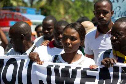 Fleurette Guerrier, the wife of missing photojournalist Vladjimir Legagneur, joins hundreds of journalists in a march to demand an investigation into why the freelance photographer vanished while on assignment, in Port-au-Prince, Haiti, March 28, 201...
