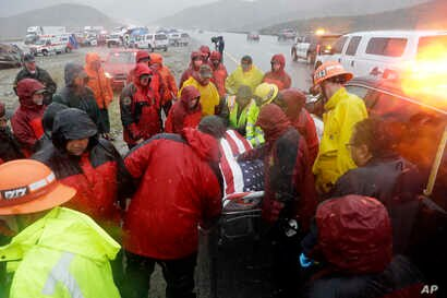 Emergency personnel huddle around the body of a volunteer member of the Ventura County search and rescue team, killed in a traffic accident along Interstate Highway 5 south of Pyramid Lake, Calif., Feb. 2, 2019.
