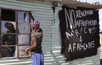 FILE - A man replaces a broken window at a tavern in Philippi township, on the outskirts of Cape Town, South Africa.