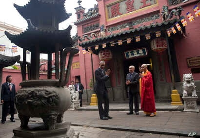 President Barack Obama stands with Thich Minh Thong, abbot of the Jade Emperor Pagoda, right, and Duong Ngoc Dung, professor at Ho Chi Minh City University of Social Sciences and Humanities, center, after visiting the Jade Emperor Pagoda in Ho Chi Mi...